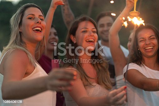 istock Friends celebrating the new year on the beach with sparkler 1089406128