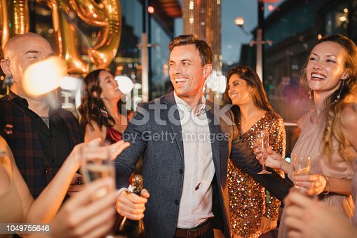 Friends celebrating the new year with a bottle of champagne and golden 2019 balloons.