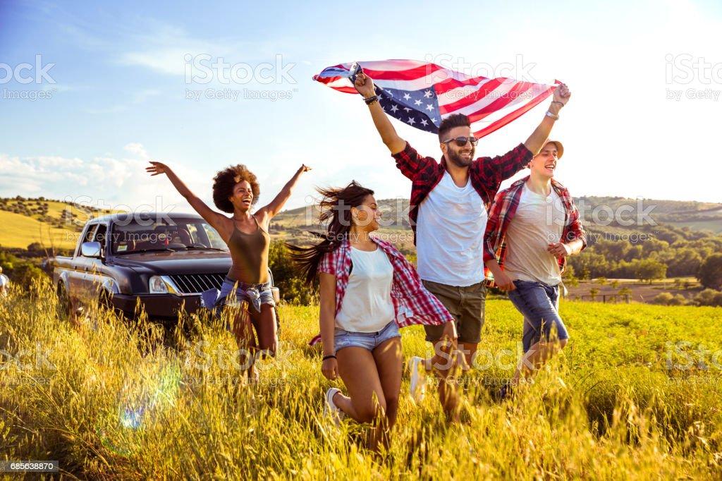 Amigos celebrando juntos sosteniendo una bandera de Estados Unidos en el campo - foto de stock