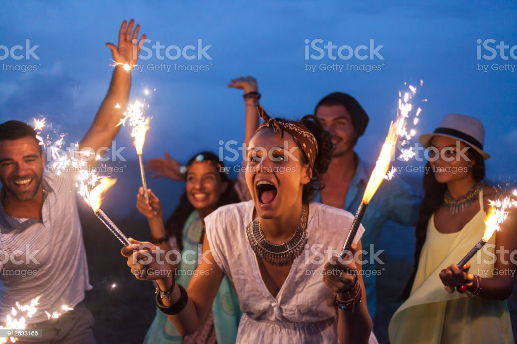 Friends celebrating with fireworks on beach at night stock photo