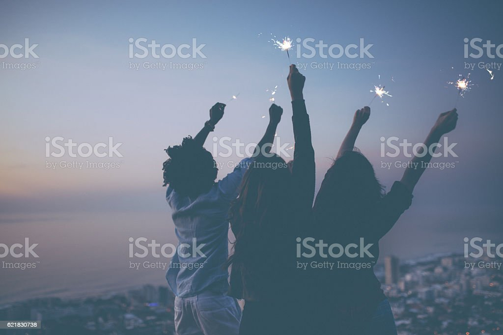 Friends celebrating with sparklers at sunset stock photo