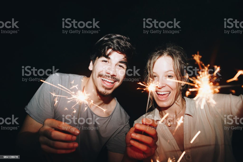 Friends celebrating with sparklers in the night stock photo