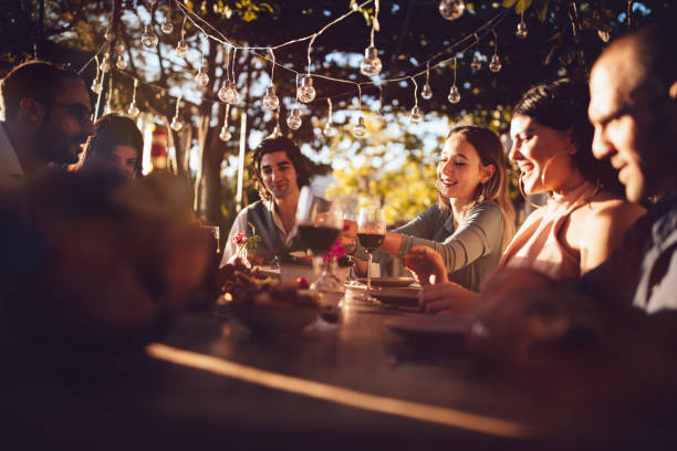 Friends celebrating with wine and food at rustic countryside party stock photo