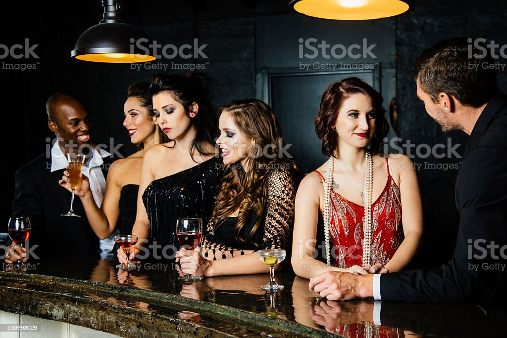 Friends chatting and having drinks together at cocktail bar stock photo