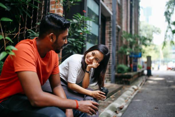 Friends chatting outdoors in Kuala Lumpur, Malaysia stock photo