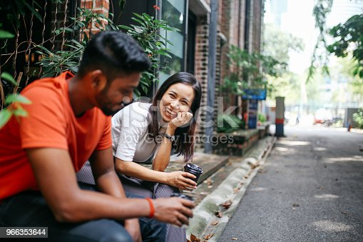 Young people talking and flirting on the streets of Kuala Lumpur, having a coffee break together in front of their office or university library.