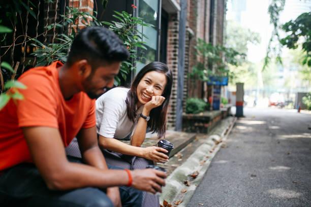friends chatting outdoors in kuala lumpur, malaysia - vicino foto e immagini stock