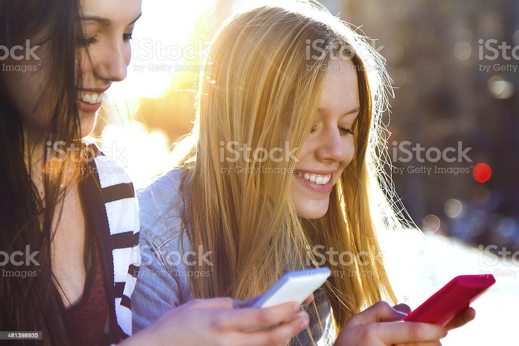 friends chatting with their smartphones stock photo