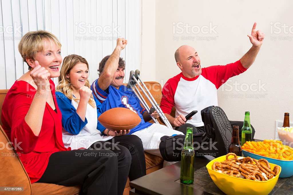 Friends cheer for their team with injured guest royalty-free stock photo