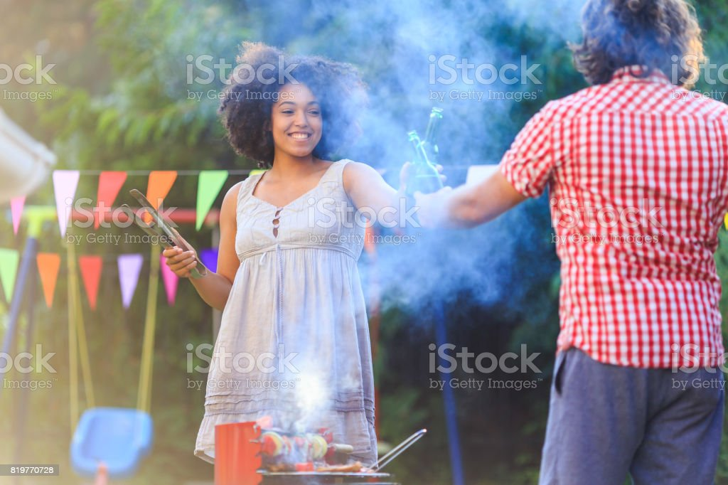 Friends cheering and making backyard barbecue stock photo