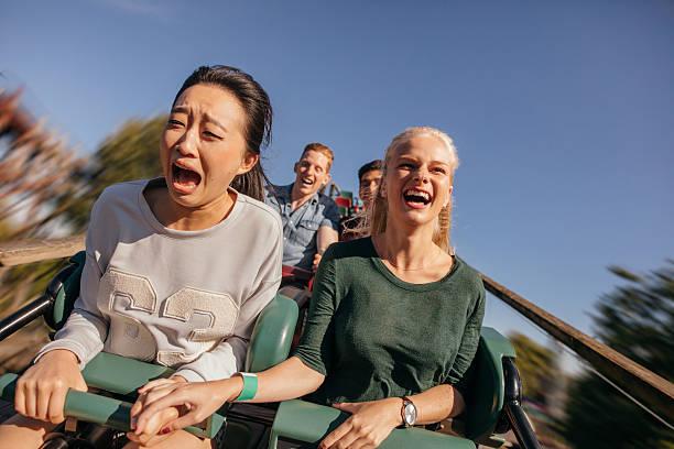 friends cheering and riding roller coaster at amusement park - roller coaster fotografías e imágenes de stock