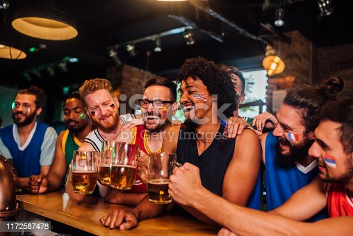 Group of guys drinking beer and cheering in a bar