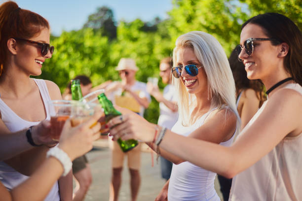 Friends cheering at the outdoor party stock photo