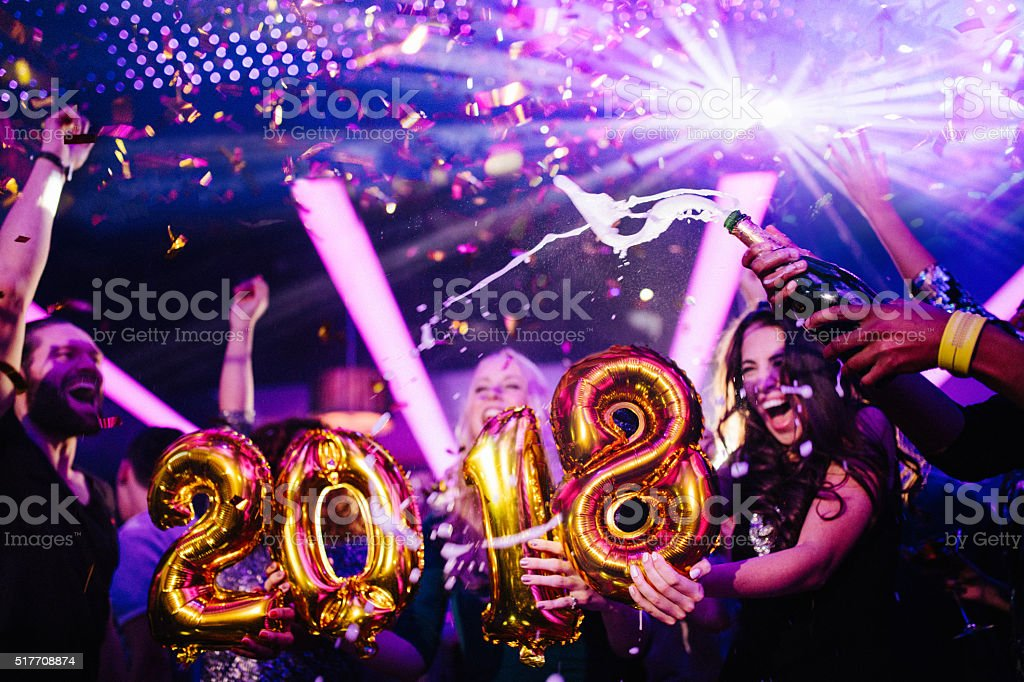 Friends cheering for New Years eve in night club party stock photo