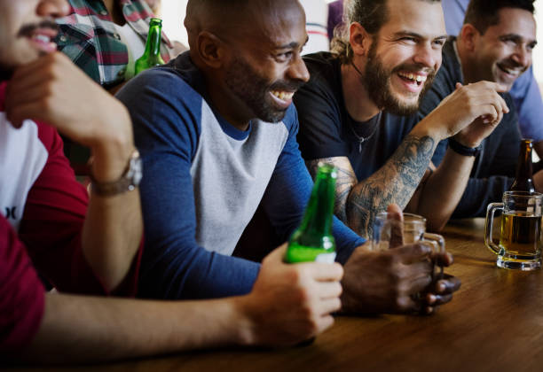 Friends cheering sport at bar together stock photo