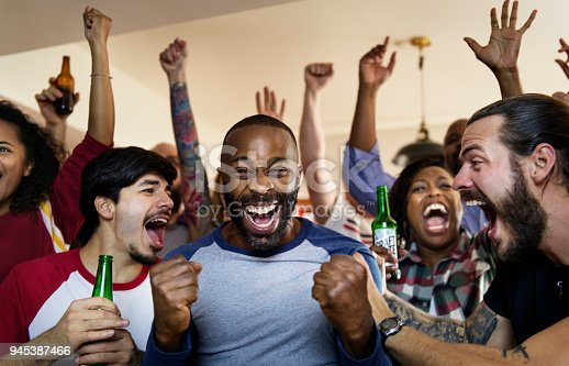 istock Friends cheering sport at bar together 945387466