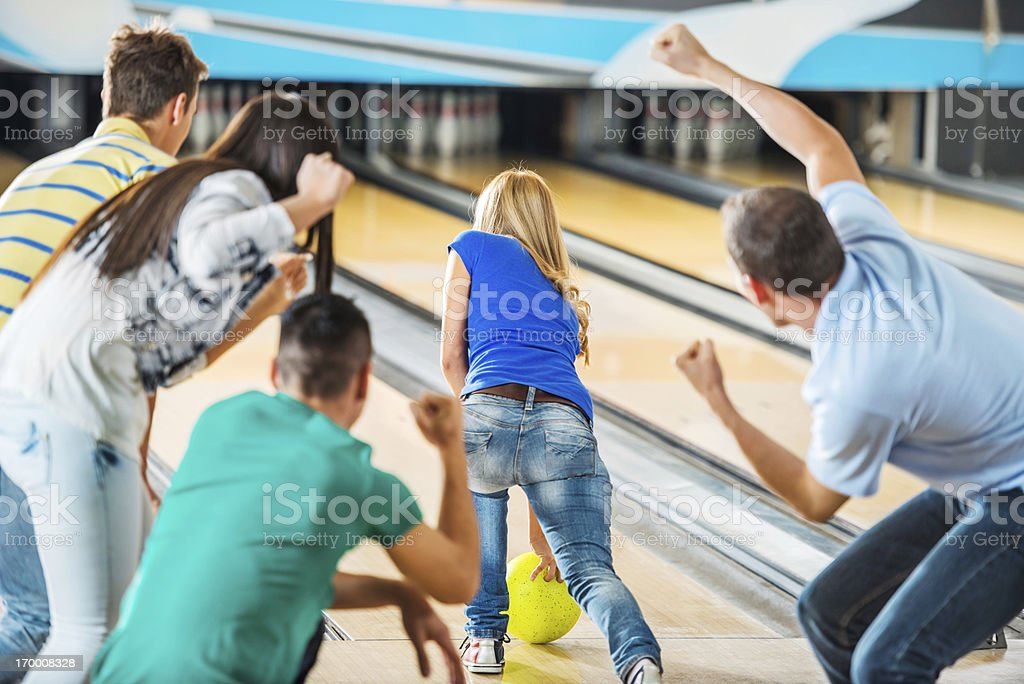 Friends cheering while girl is throwing a bowling ball. stock photo