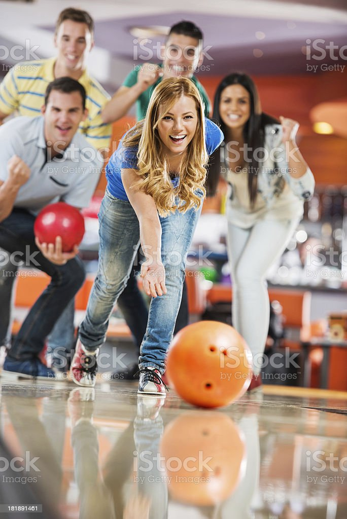 Friends cheering while girl is throwing a bowling ball stok fotoğrafı