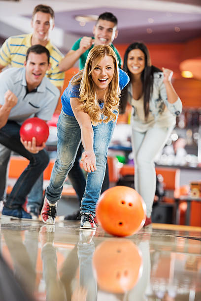 Friends cheering while girl is throwing a bowling ball stock photo