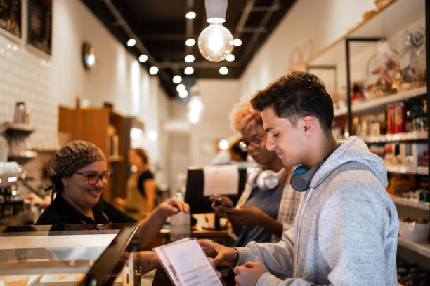 friends choosing menu in coffee shop - small business saturday stock pictures, royalty-free photos & images
