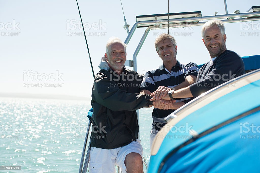 Friends clasping hands on deck of boat royalty-free stock photo
