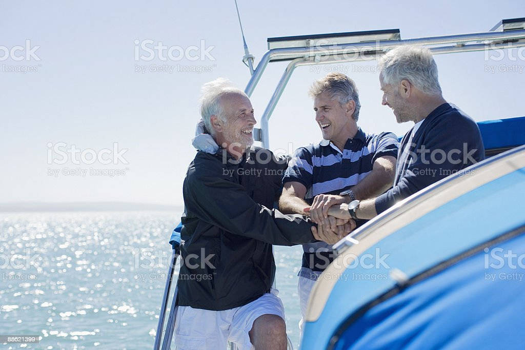 Friends clasping hands on deck of boat stock photo