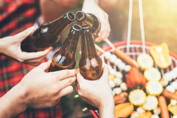Friends clinking bottle of beer during party stock photo