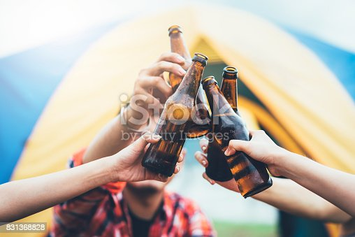 Friends clinking bottle of beer during travel camping trip outdoor