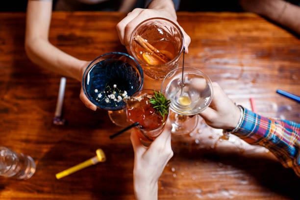vrienden klinken met een bril met diverse alcoholische cocktails aan tafel - cocktail stockfoto's en -beelden