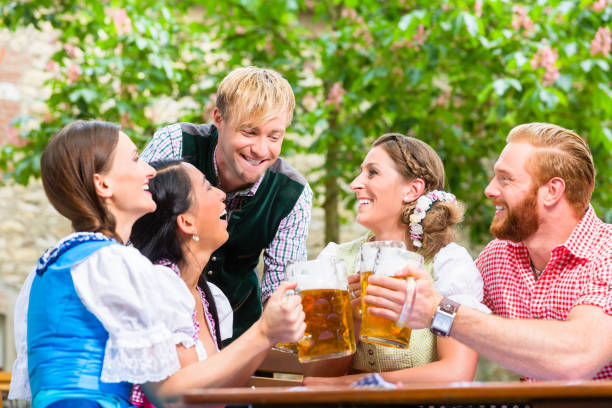 Friends clinking glasses in beer garden stock photo
