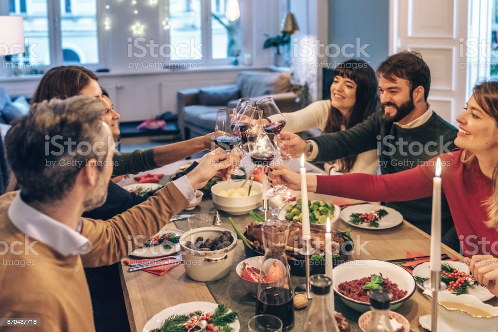 friends clinking wine glasses at festive christmas table stock photo