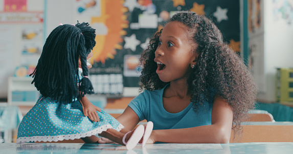 Shot of a young girl playing with a doll in a classroom at school