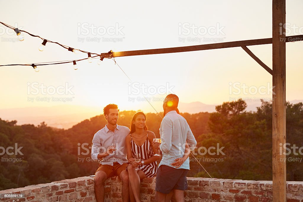 Friends communicating at patio during sunset stock photo