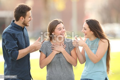 istock Friends congratulating a happy girl in the street 1145855957