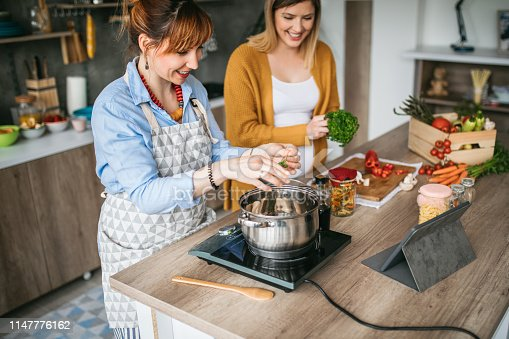 Pregnant woman cooking together with her best friend