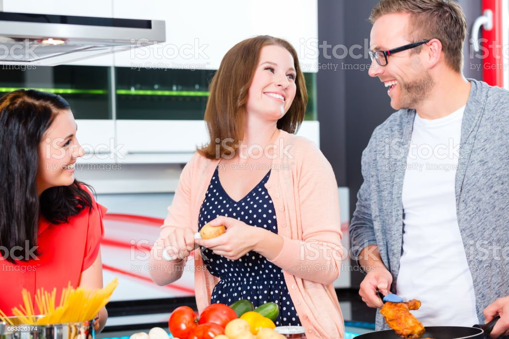 Friends cooking pasta and meat in domestic kitchen royalty-free stock photo