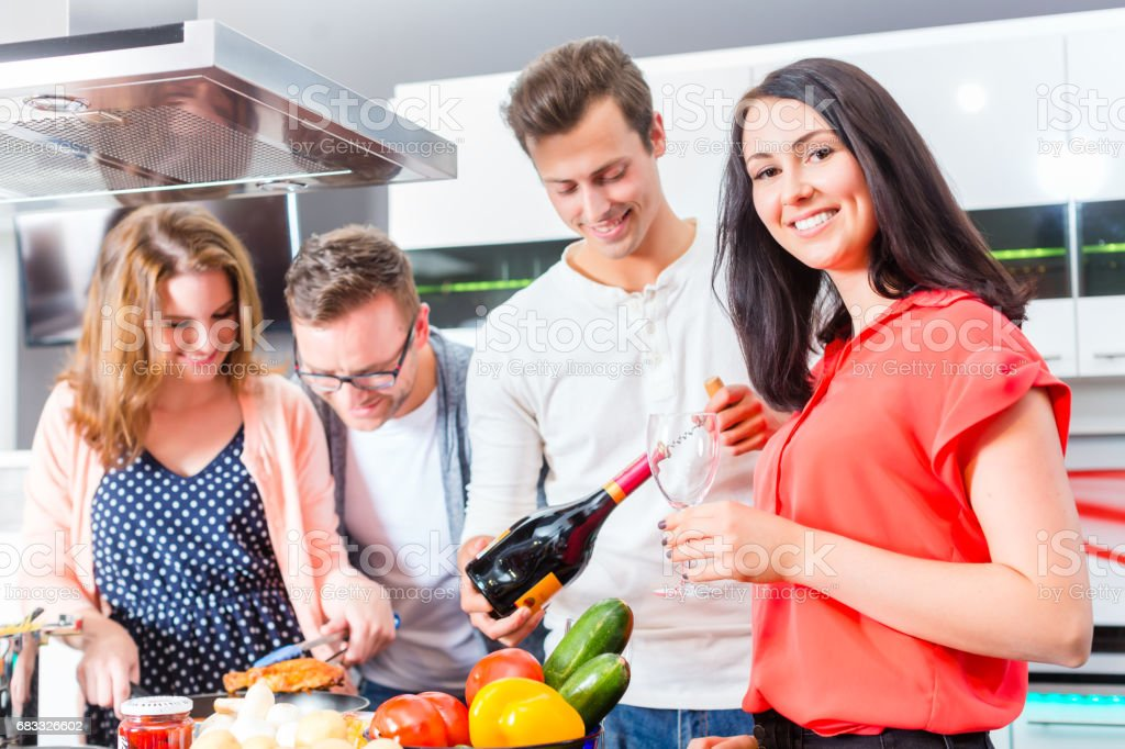 Friends cooking pasta and meat in domestic kitchen foto stock royalty-free