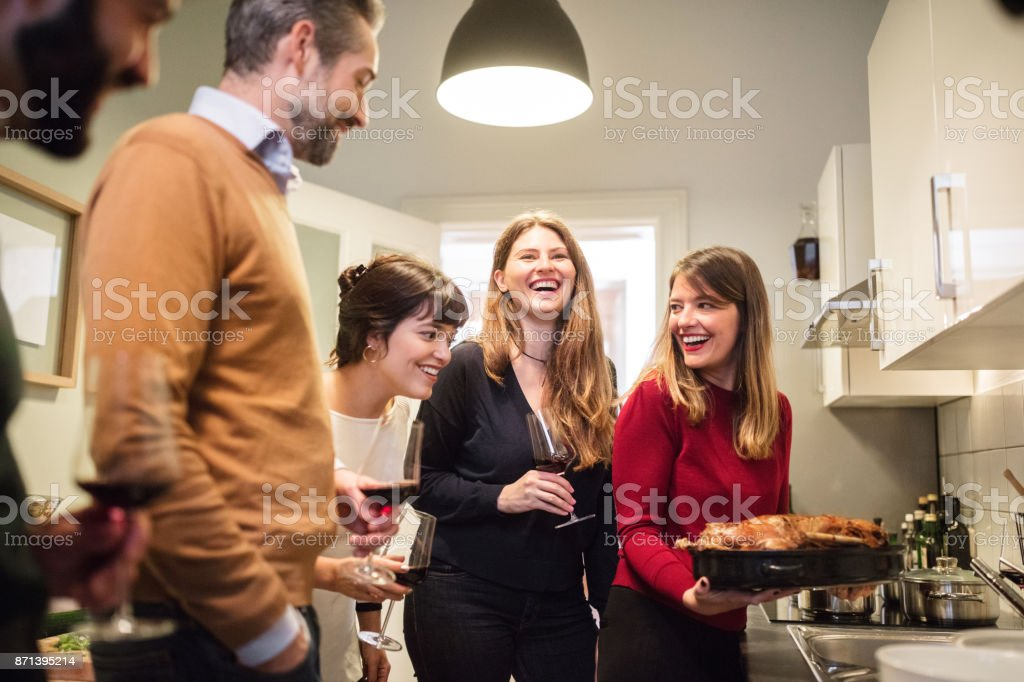 friends cooking poultry in kitchen for Christmas party stock photo