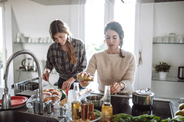 friends cooking together at home - foodie stock photos and pictures