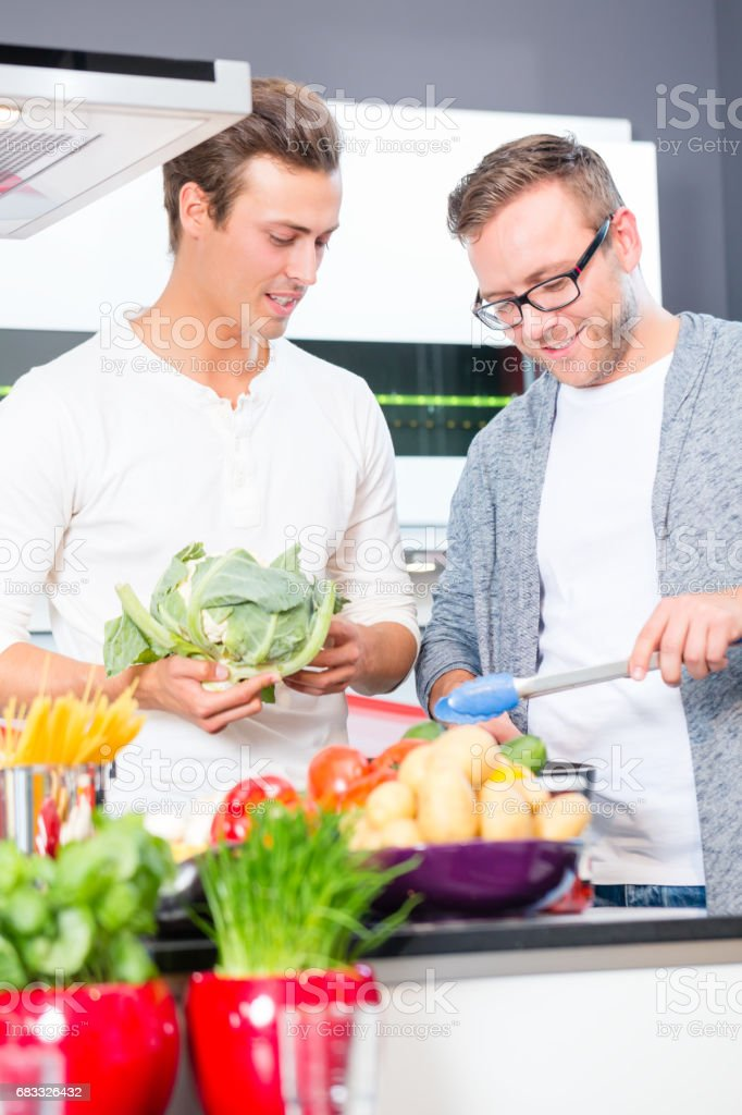 Friends cooking vegies and meat in domestic kitchen stock photo