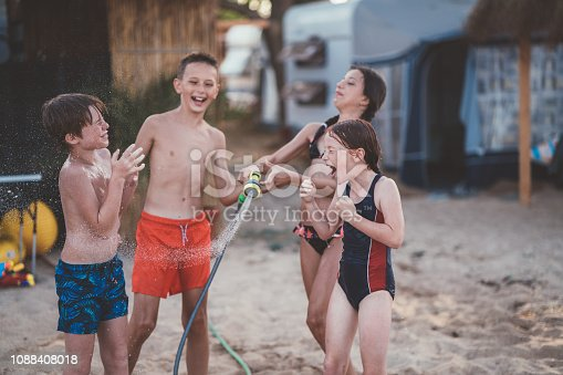 Kids playing at the beach with garden hose