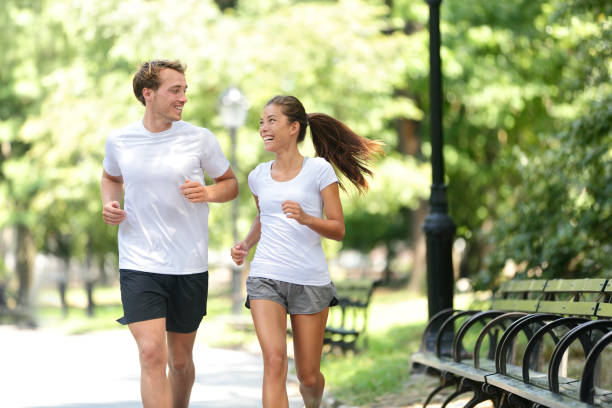 Friends couple happy running together in city park stock photo