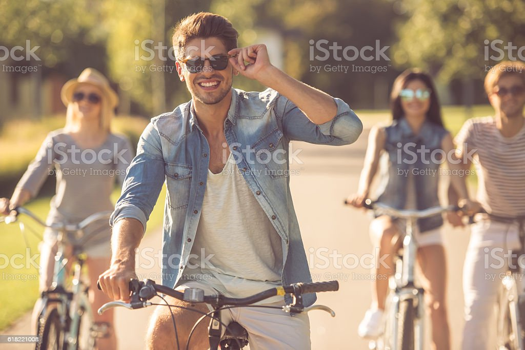 Friends cycling in park stock photo