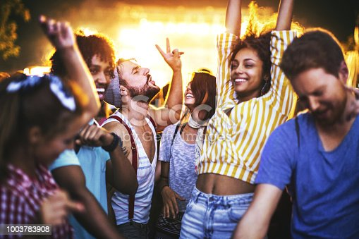 Closeup of group of multi ethnic young adults dancing and enjoying an open air concert on a summer night. There are three girls and three guys in a candid shot against bright background light.