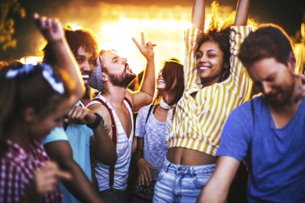 Friends dancing at a concert. Closeup of group of multi ethnic young adults dancing and enjoying an open air concert on a summer night. There are three girls and three guys in a candid shot against bright background light. nightclub stock pictures, royalty-free photos & images