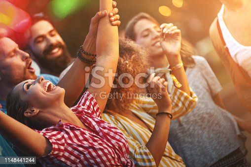 Closeup side view of group of young adults dancing and enjoying an open air concert on a summer afternoon. There are three girls and three guys enjoying this party on a summer afternoon.
