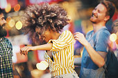 Closeup of group of multi ethnic young adults dancing and enjoying an open air concert on a summer afternoon. There's african american girl in the focus with some motion blur and couple of her friends on the side.
