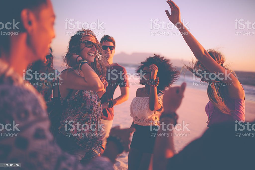 Friends dancing at a summer sunset beachparty stock photo