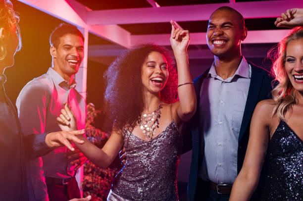 Friends dancing at party Cheerful girl dancing at night party with her friends. Beautiful young woman and smiling men having fun at nightclub. Group of multiethnic young people at club having fun at new year's eve. nightlife stock pictures, royalty-free photos & images