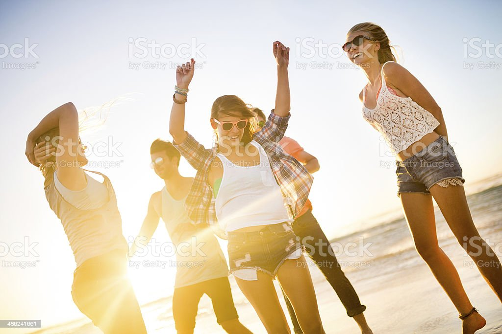 Friends dancing on beach in sunset stock photo